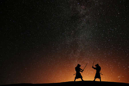 Silhouette of two samurais against the starry sky. Deadly warriors with swords