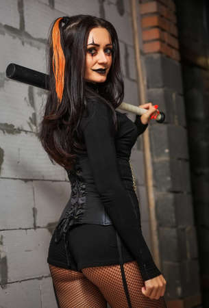 A woman with a beisball bat on a Halloween party. Bad girl with a weapon in their hands.