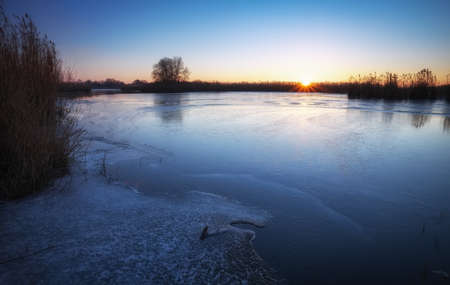 Winter landscape with frozen river, reeds and sunset sky. Daybreak Stock Photo