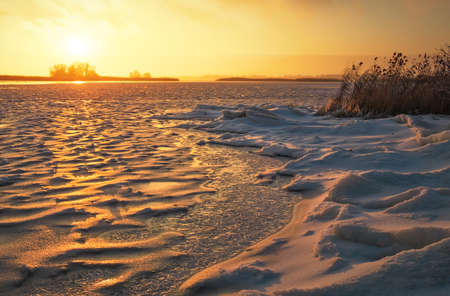 Winter landscape with frozen lake and sunset fiery sky. Composition of nature.