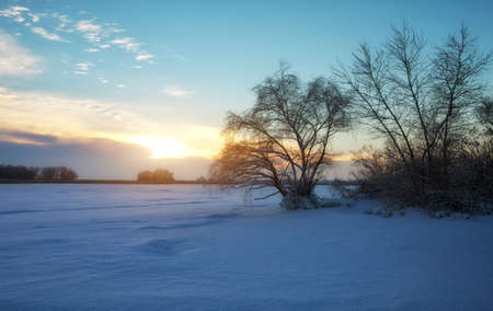 Beautiful winter landscape with frozen lake, trees and sunset sky Stock Photo