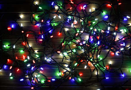 Holiday garland at night. Christmas background - wood with colorful lights.  Top view.