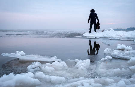 Man with backpack on the coast of frozen river during sunset. Traveler concept Stock Photo
