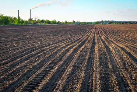 Preparing field for planting. Plowed soil in spring time, two tubes and blue sky.