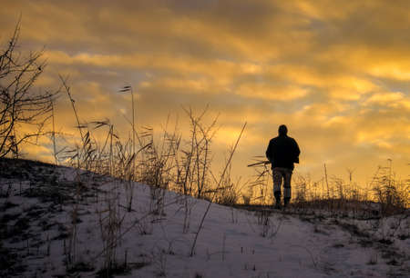 Winter hunting at sunrise. Hunter moving With Shotgun and Looking For Prey. Reklamní fotografie