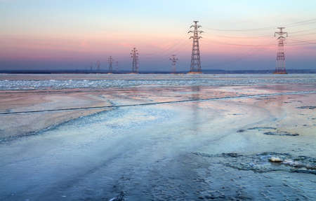 High-voltage lines in frozen lake, goes from city