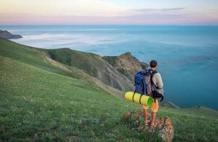 Young tourist on top of a mountain enjoying sea view.  Stock Photo