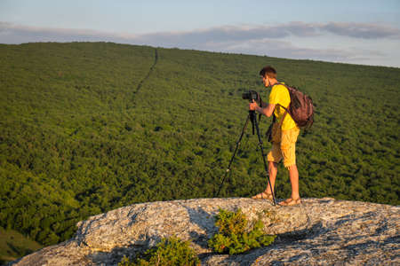 Photographer with tripod and backpack on the rock in the evening.