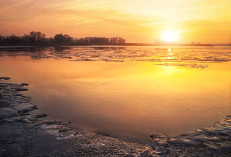 Beautiful colorful winter landscape with frozen lake and sunset sky.