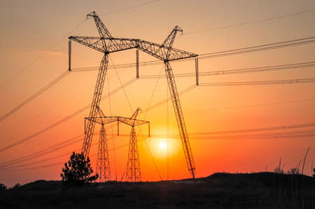 High-voltage power lines during fiery sunrise Stock Photo