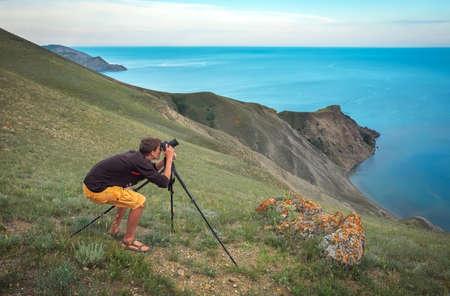 A photographer with a tripod and camera makes photos of landscapes on the mountain. Men in work. Stock Photo
