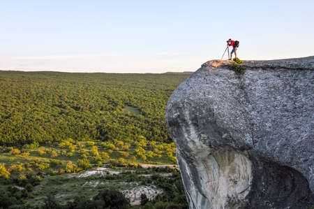 The photographer takes pictures of the scenery on the rock in the evening.
