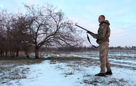 Winter hunting. Hunter moving With Shotgun and Looking For Prey. Stock Photo