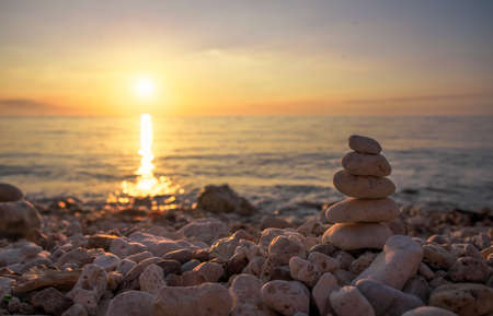 Pyramid of the small pebbles on the beach. Stones, against the background of the sea shore during sunset Stock Photo