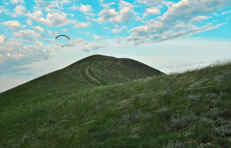 Trike with a parachute against the blue sky. Paragliding flying over the clouds 版權商用圖片