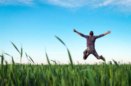 Young man jumping for joy over a green wheat field. Handsome farmer. Spring agriculture. Man admires the beauty of nature