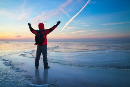 Nature photographer traveler on the frozen lake during sunrise in winter. Beautiful colorful landscape with people 写真素材
