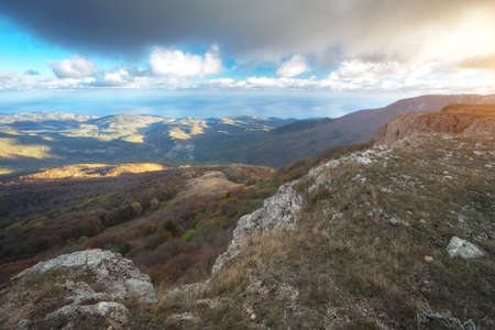 Landscape from mountain peak with sea and majestic clouds in sky