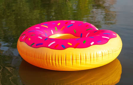 Big inflatable donut on water in sunrise time. Hipster sprinkled donut float in lake