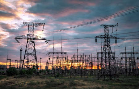 Electric substation with power lines and transformers, at sunset
