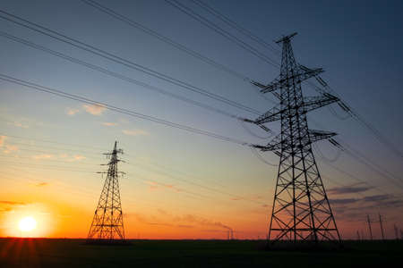 Silhouette High voltage electric towers at sunset time. High-voltage power lines. Electricity distribution station