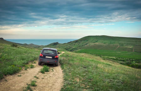 Dirty car crossover. Fields with vineyards. Beautiful nature with hills. Black Sea in the background. 版權商用圖片