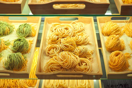 Various mix of uncooked pasta in on wooden tray in the shop window. Different kind of dry macaroni in round form. Italian foods concept of spaghetti and menu design