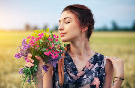 Cute attractive girl with a bouquet of colorful flowers in her hands. Young woman breathes in the scent of plants on wheat field during sunset. Pensive look. Romantic atmosphere. Banco de Imagens