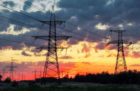 Tours électriques à haute tension de silhouette au moment du coucher du soleil. Lignes électriques à haute tension. Poste de distribution d'électricité Banque d'images