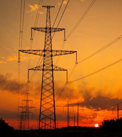 Silhouette Hochspannungs-Strommasten bei Sonnenuntergang. Hochspannungsleitungen. Stromverteilungsstation Standard-Bild