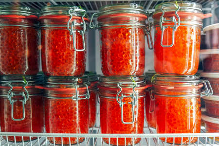 Jars with delicious red caviar in the fridge. Delicious expensive snack