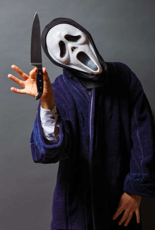 The man in white mask threatens with knife, killer concept, horror theme , Halloween concepts