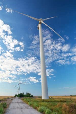 Turbiny wiatrowe i pola uprawne w pochmurny letni dzień. Produkcja energii, czysta i odnawialna energia.
