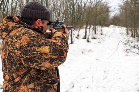 Hunter with a sniper rifle in the winter forest. A man is looking for a target Reklamní fotografie