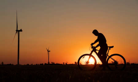 A cyclist with a camera stands in a field during the sunset against the background of an orange sky with the sun and windmills Stok Fotoğraf
