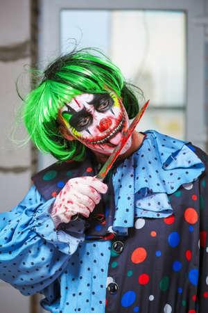 Clown fou avec un couteau sur un fond de mur de briques. Notion d'Halloween