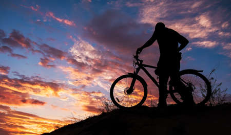 Silhouette of sports person cycling on the meadow on the beautiful sunset. Young man riding bicycle. 스톡 콘텐츠
