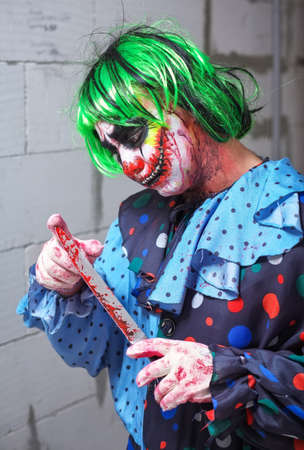 Crazy clown with a knife on a brick wall background. Halloween concept