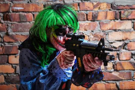 Payaso loco con una pistola sobre un fondo de pared de ladrillo. Concepto de halloween