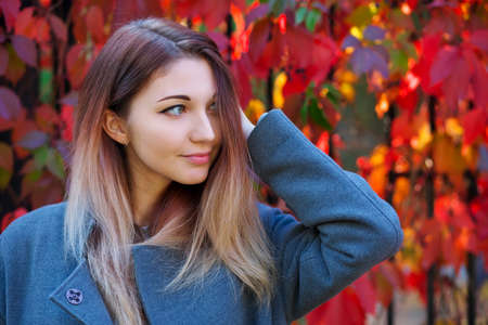 Dreamy beautiful girl with long colorful hair on autumn background of red grape hedge. Inspired woman in gray coat. Autumn euphoria. Female emotional portrait in faded tones. 免版税图像