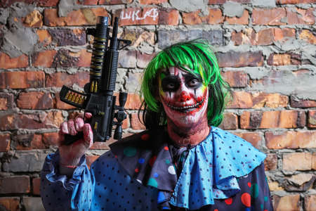 Crazy clown with a gun on a brick wall background. Halloween concept