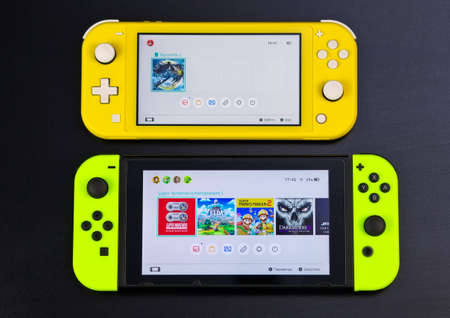 MOSCOW, RUSSIA - October 10, 2019: Nintendo Switch and small Nintendo Switch Lite. Comparison of two handheld game consoles