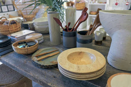 Vintage dishes and other original things on a wooden table. Plates, baskets, vases, books