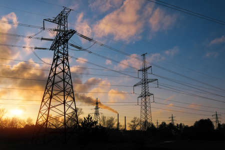 High-voltage power lines during fiery sunrise