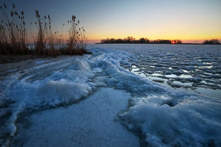 Sunrise and frozen river. Beautiful winter landscape with lake in morning time. Daybreak