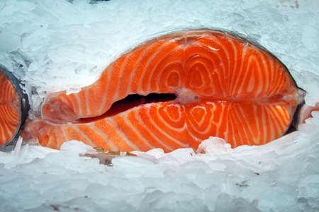 A piece of red fish in ice close-up. Sectional salmon. Archivio Fotografico
