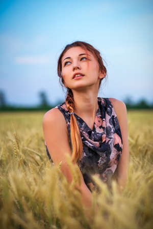 Cute attractive young girl on wheat field during sunset. Pensive look. Romantic atmosphere.