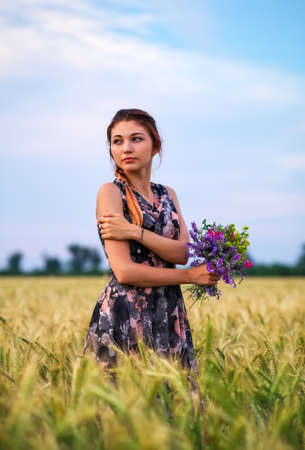 Cute attractive girl with a bouquet of colorful flowers in her hands. Young woman breathes in the scent of plants on wheat field during sunset. Pensive look. Romantic atmosphere. Archivio Fotografico