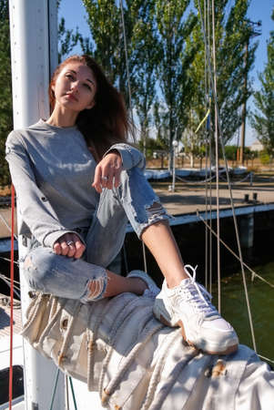 Beautiful young woman posing on yacht. Model is sailing on board.