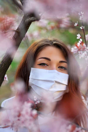 Close up portrait of young girl under a blossoming apricot tree with a mask from the coronavirus. Imagens - 148379476